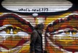 A man walks by a mural in Athens, Greece July 14, 2015, REUTERS/Yannis Behrakis